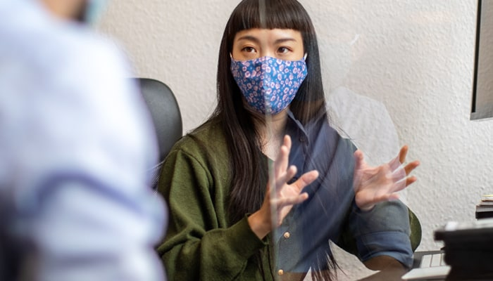 Woman seated at desk wearing mask
