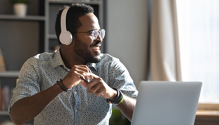 Man wearing headphones working on laptop