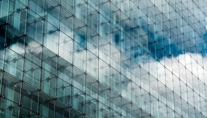 Side of glass office building with reflection of clouds across the windows