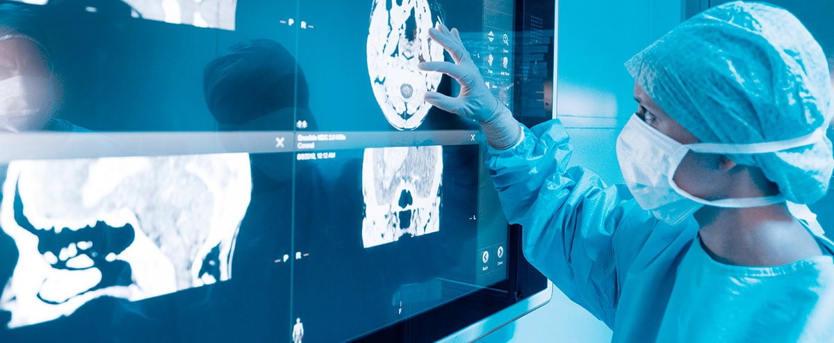 Doctor looking at x-ray results at big display