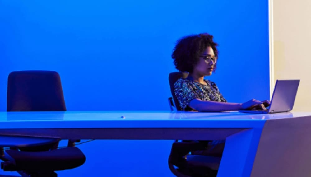 Woman on laptop in conference room with blue lighting in