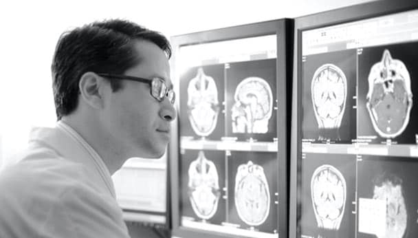 a man analyzing brain scans on a computer screen