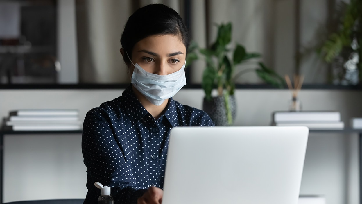 a professional wearing a mask works with a laptop computer