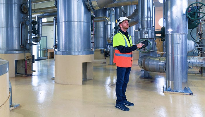 Man inspecting factory pipes and machinery