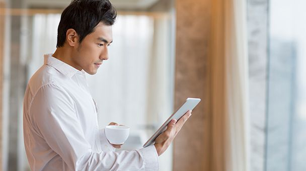 Man watching the tablet he holds in one hand