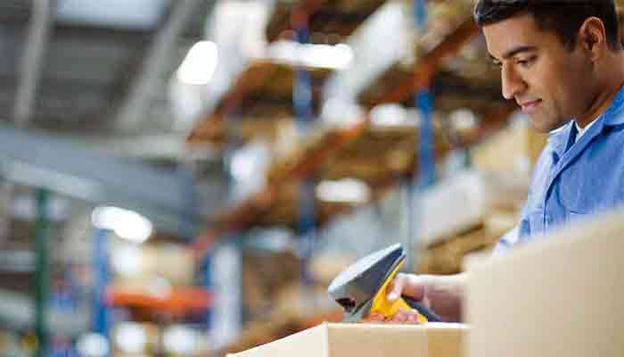 Shipping worker scanning a package within a warehouse