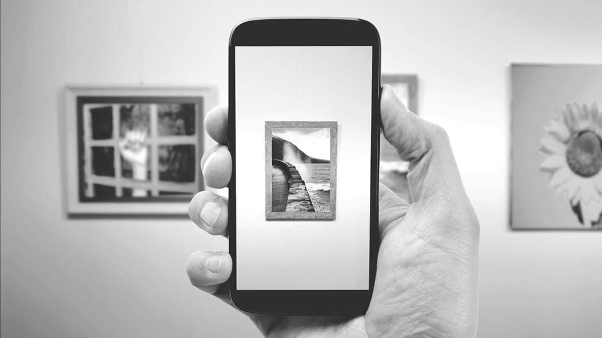 Hand holding up a smartphone showing a photo image