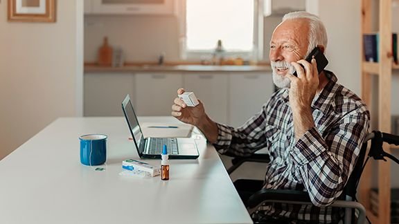person in wheelchair talking on telephone with medicine bottles on table