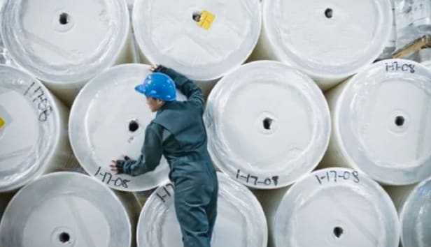 Worker in a paper mill in front of stacks of enormous rolls of paper
