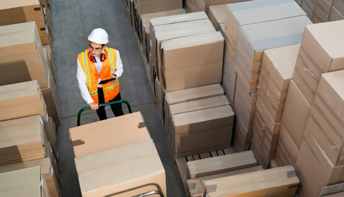 Man moving boxes in warehouse