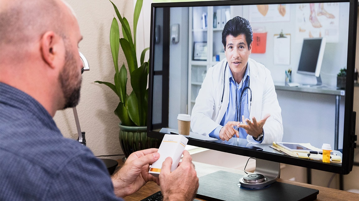 Man using video chat to discuss healthcare with his physician
