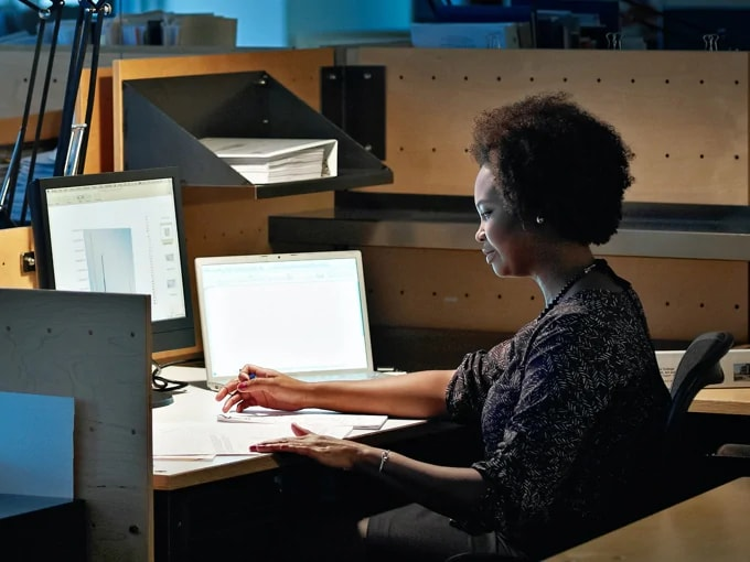African-American woman sitting at a desk looking at multiple computer screens