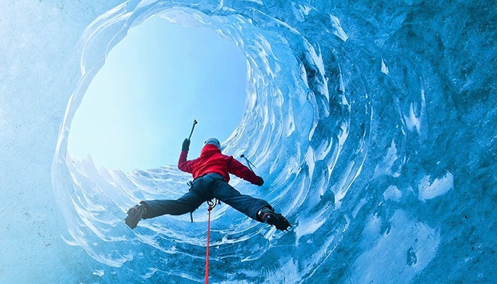 Person climbing ice cliff