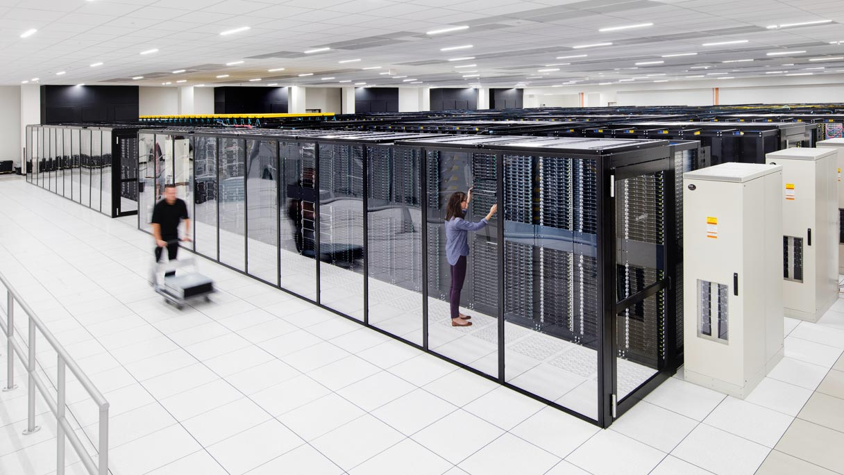 People inside a server room, moving and installing servers