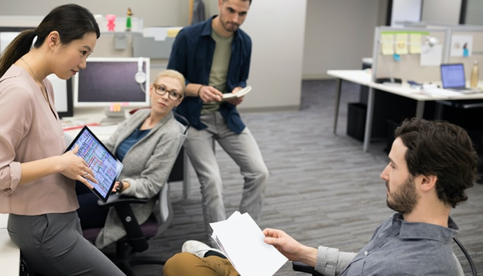 Four people talking in office setting
