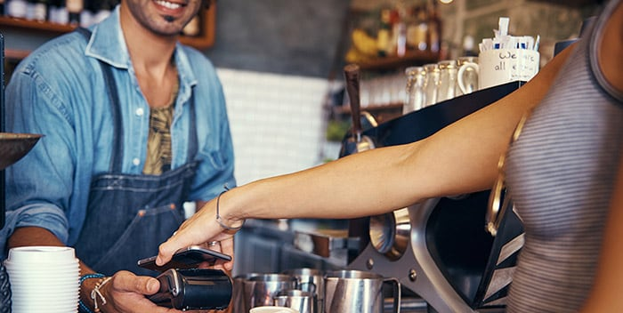 Person paying for coffee with mobile payment app