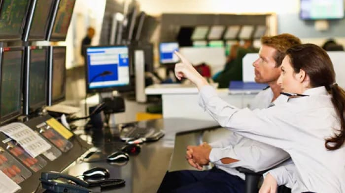 air traffic control workers pointing at screen