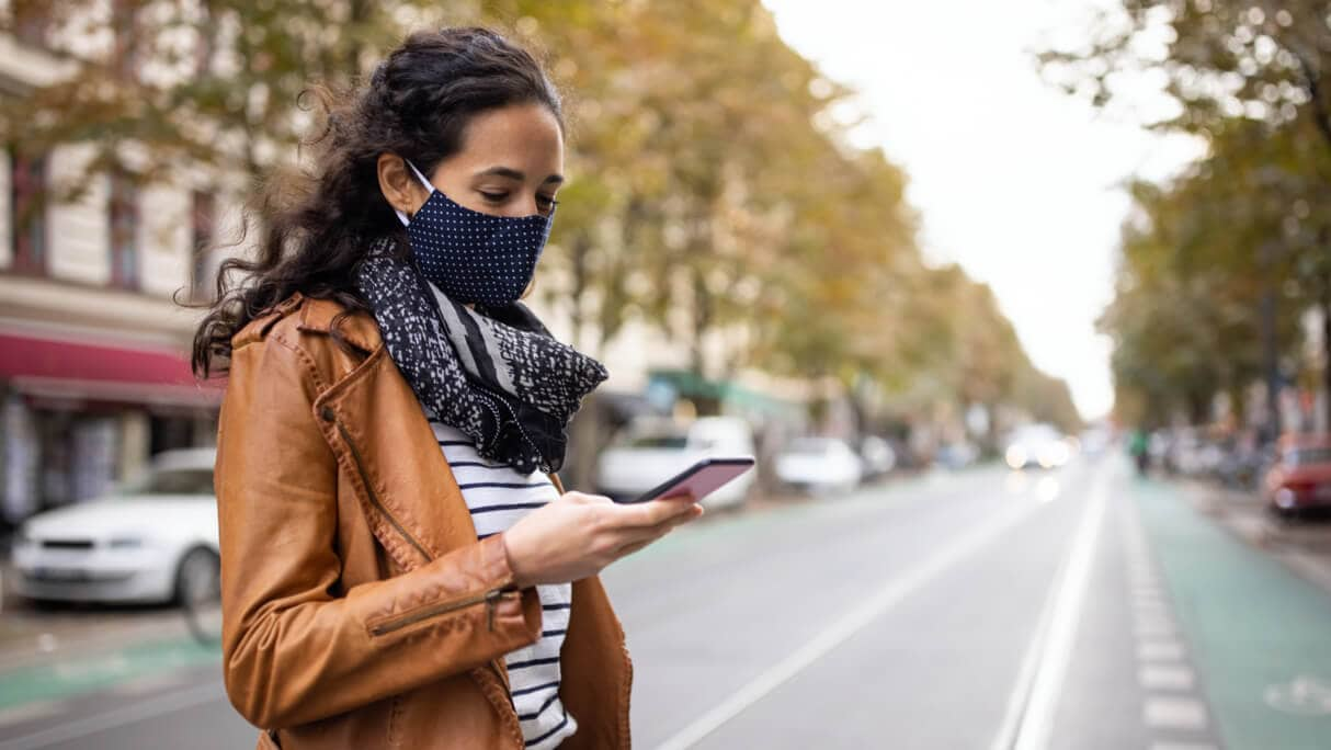 A woman wearing mask looking at her phone