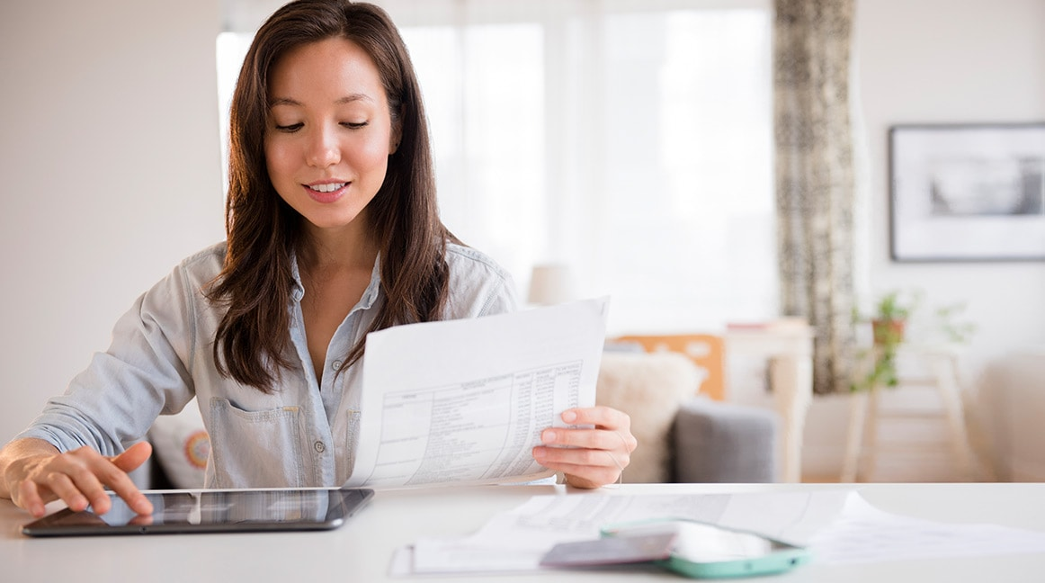 Woman comparing financial records on tablet to printouts