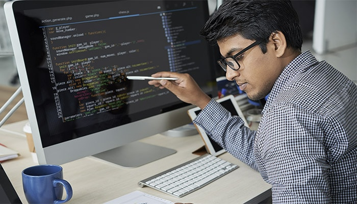 Man inspecting lines of code on a computer screen