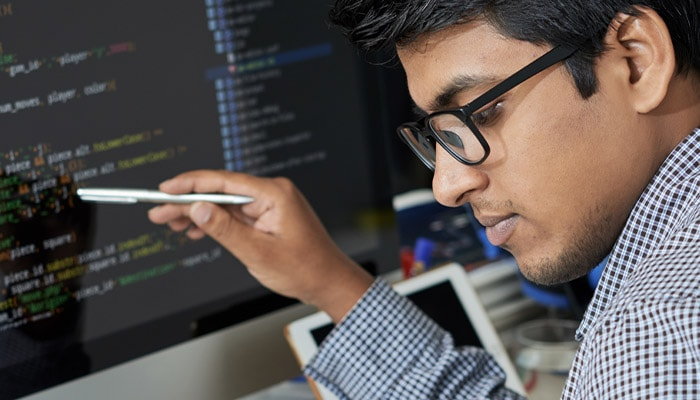Software engineer checking his work on a computer screen