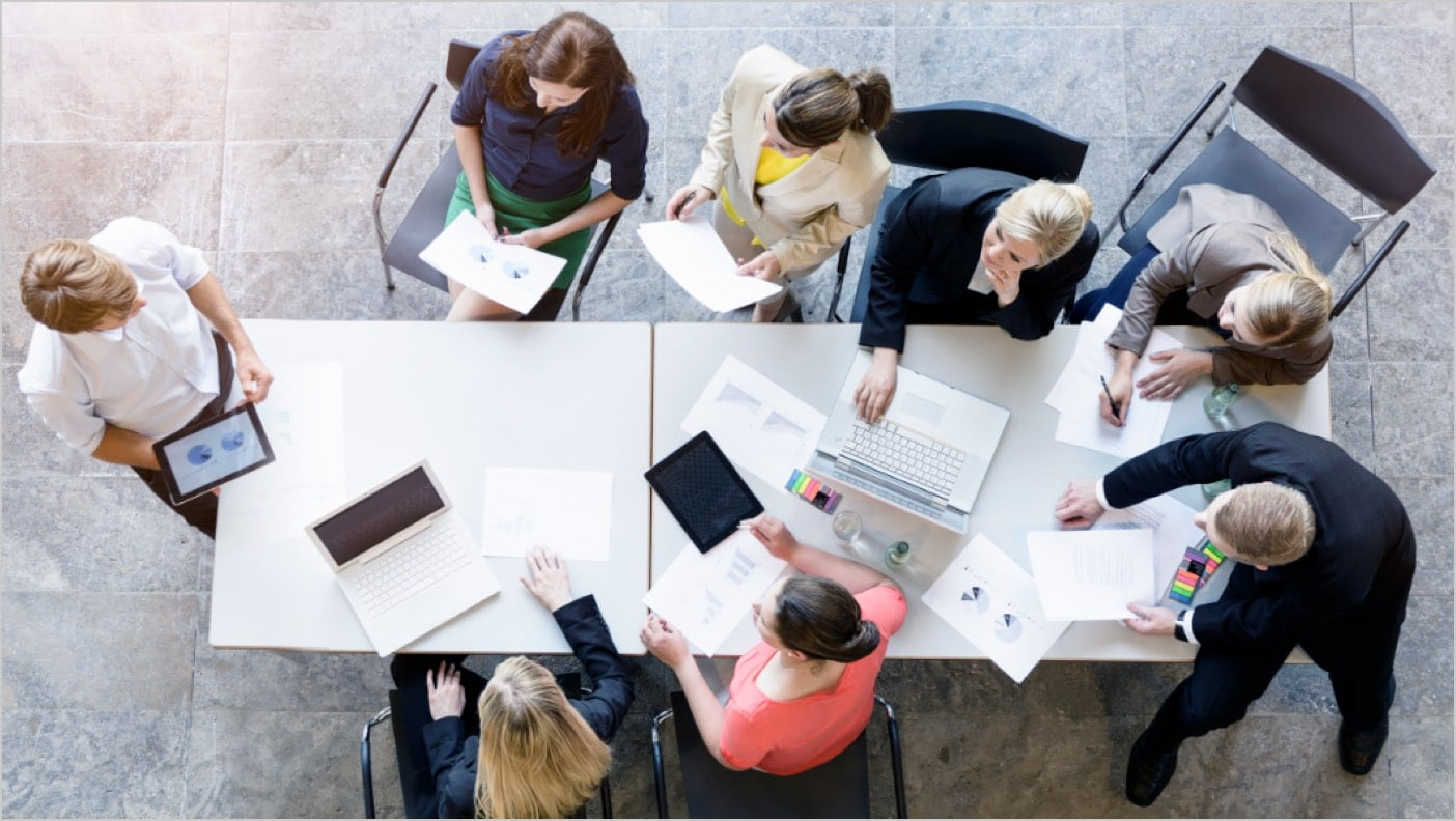 Overhead photo of businesspeople sitting around a table listening to a presentation and sharing papers
