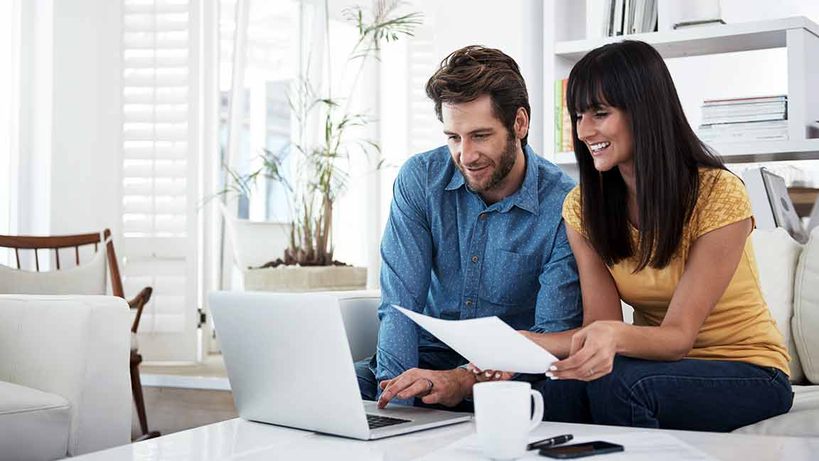 Smiling man and woman looking at a laptop