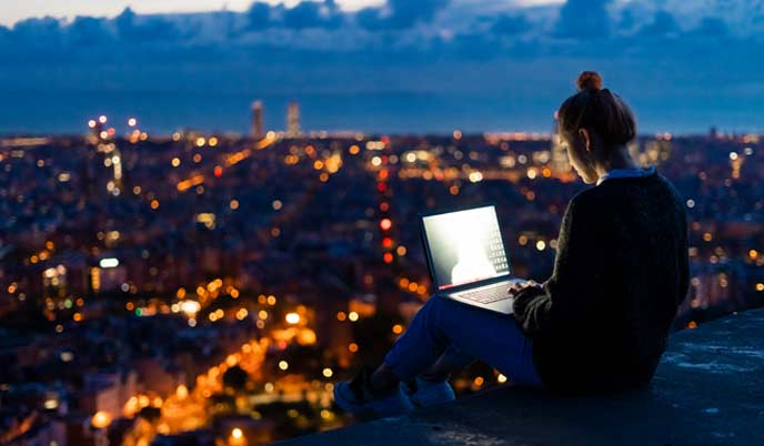 woman using a computer on the rooftop