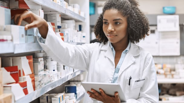 A female pharmacist with a clipboard reaching for a prescription on a shelf