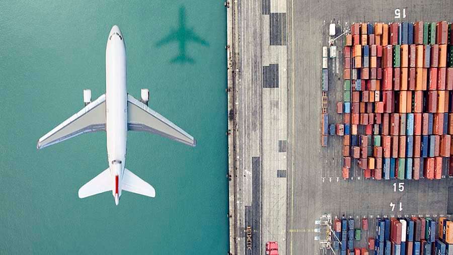 airplane flying over a container port