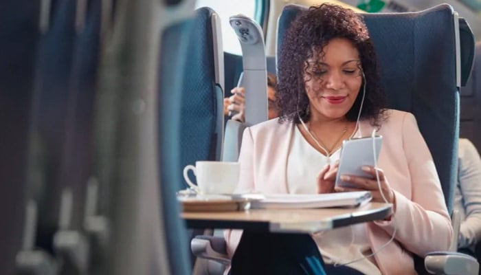 woman in a plane seat smiling at her phone