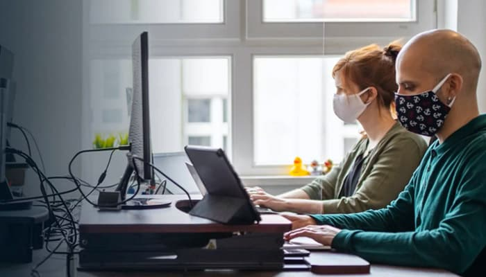 Office workers in their desk wearing masks