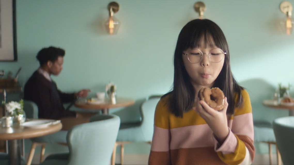 A girl eating a hybrid donut