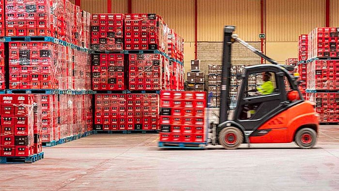 A fork lift moves bottles in a warehouse