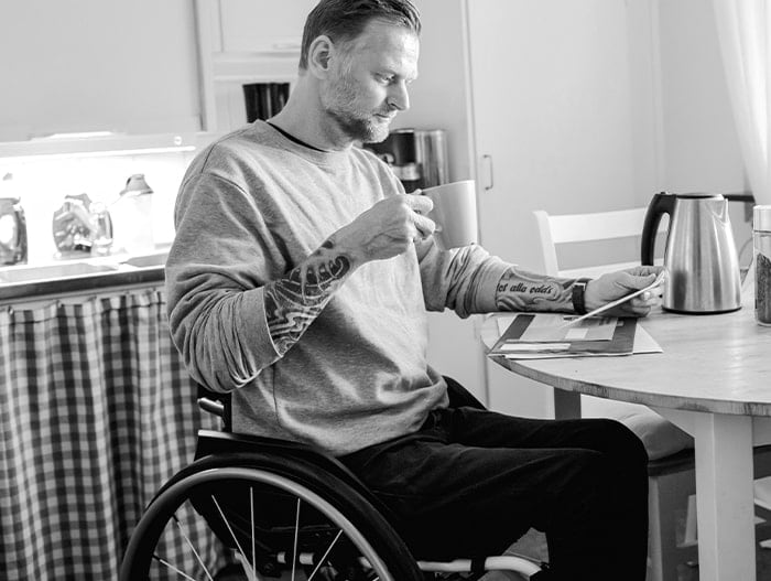 a man on a wheelchair having coffee and reading