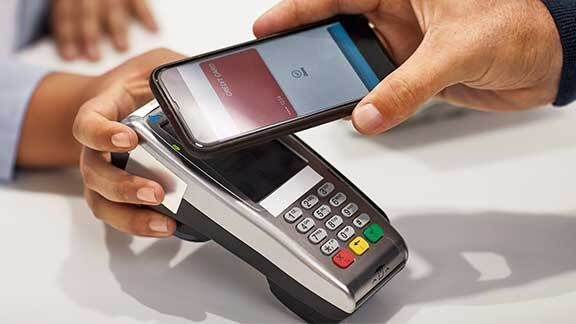 a hand holding a cellular telephone over a cash register payment machine