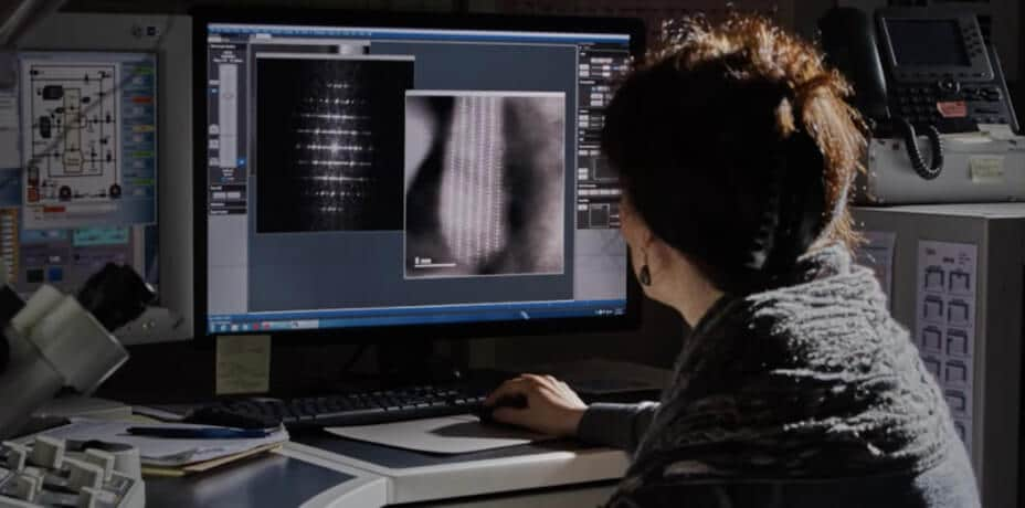 A woman looking into data in a monitor