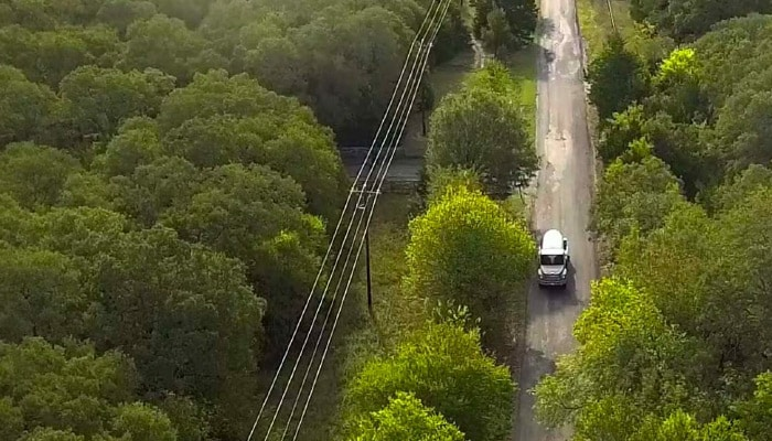 Aerial view of large truck on tree-lined highway