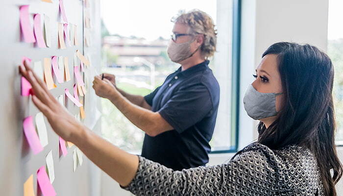 people with mask using post its on a board