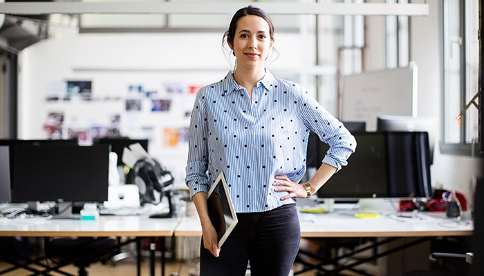 Female standing with laptop in hands at office