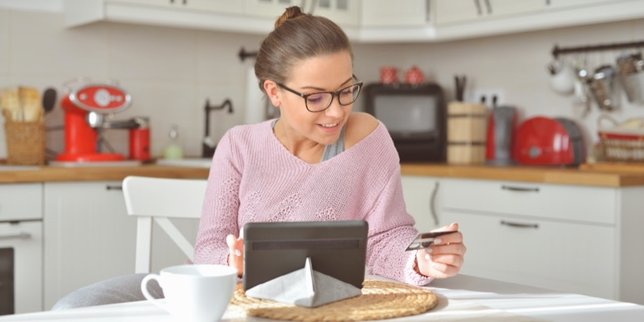 Woman holding a credit card and typing in a tablet at a kitchen