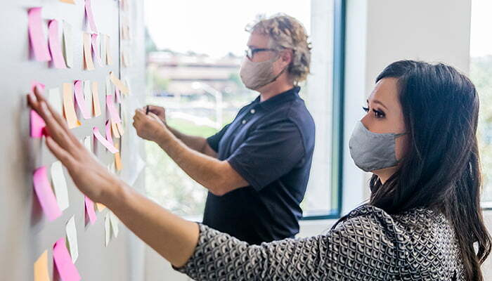 man and woman wearing masks and manipulating sticky notes at a project planning board