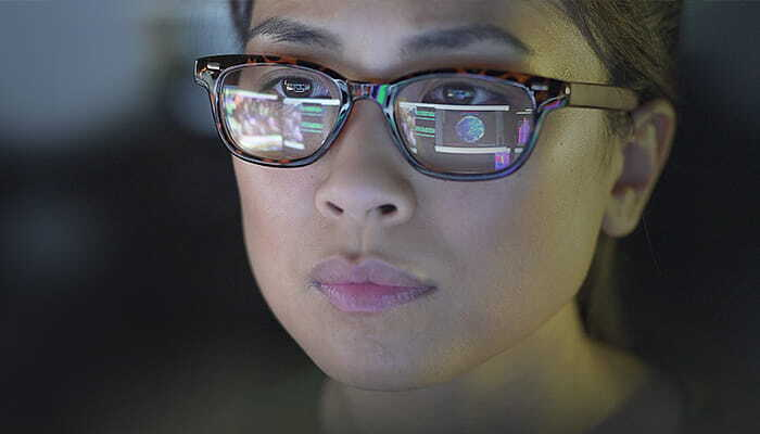woman's glasses reflecting computer screen