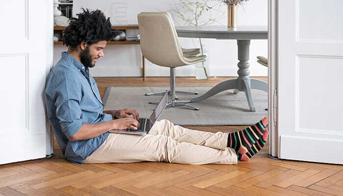 man sitting on floor working on laptop