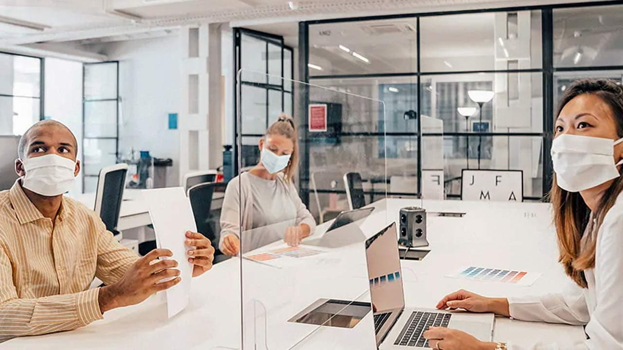 people wearing a mask in a conference room