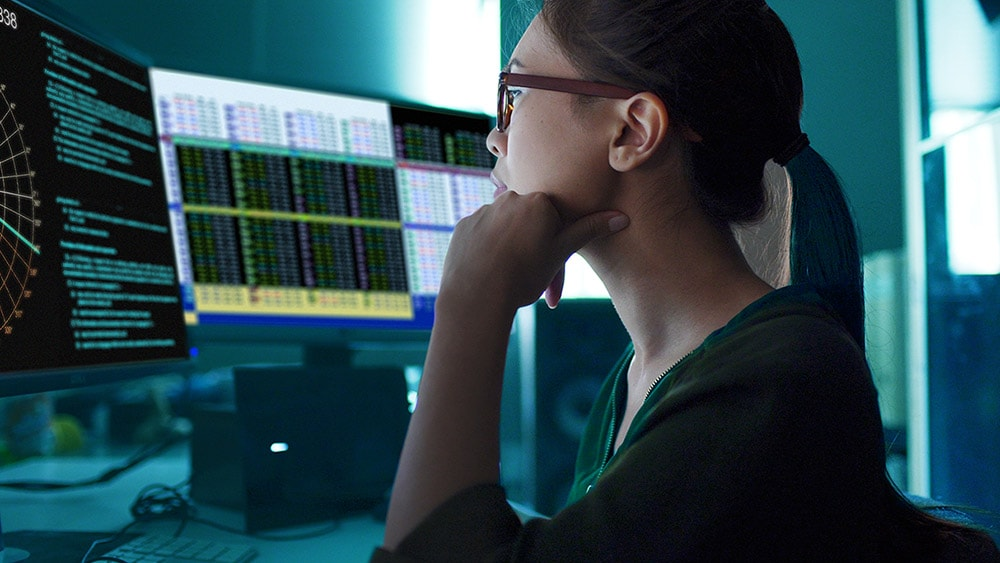 Person in front of multiple computer monitors