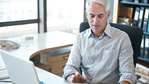 Businessman at desk in office reviewing information