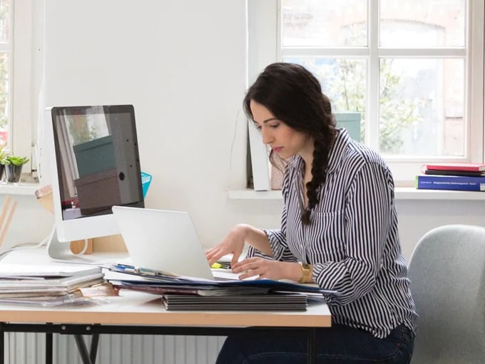 Woman sitting at a desk with files on it in front of a window, looking a laptop, with a monitor to her right.