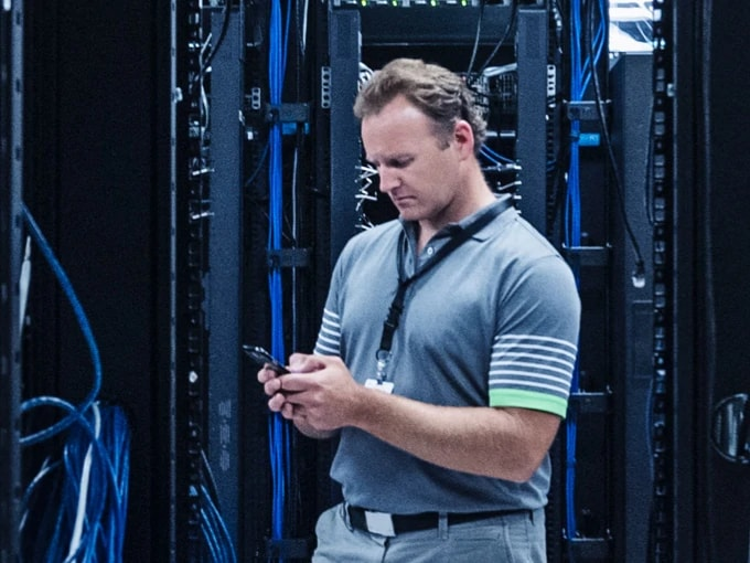Man standing in a server room, holding and looking at a mobile phone