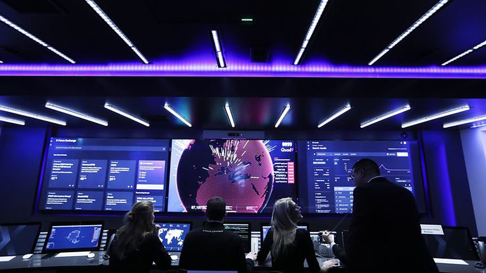Three people gathered in a war room